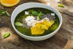 绿色圆滑的人碗用香蕉、菠菜、chia种子和桔子 库存图片