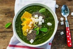 绿色圆滑的人碗用香蕉、菠菜、chia种子和桔子 免版税库存图片