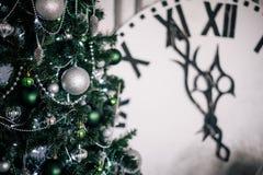 绿色圣诞树在背景中是显示午夜的一个大装饰时钟 库存照片