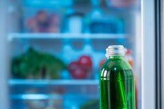 绿色在冰箱门的瓶用汁液或苏打 库存图片