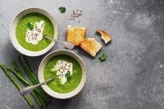 绿色奶油色芦笋汤用在灰色背景的酥脆多士 E 免版税库存照片