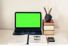 绿色屏幕膝上型计算机、堆书,智能手机、笔记本和铅笔在白色桌,教育办公室概念背景上 免版税库存照片