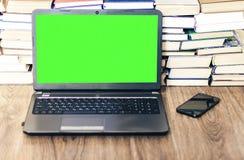 绿色屏幕膝上型计算机、堆书,智能手机、笔记本和铅笔在白色桌,教育办公室概念背景上 免版税库存图片