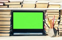 绿色屏幕膝上型计算机、堆书,笔记本和铅笔在白色桌,教育办公室概念背景上 库存照片