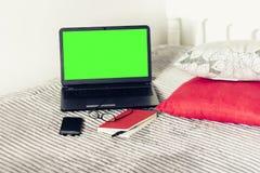 绿色屏幕膝上型计算机、笔记本、智能手机、玻璃和笔在坏,教育概念背景 库存图片