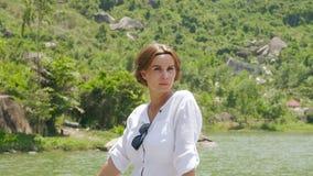 绿色山和夏天河的画象女孩环境美化 放松在湖岸和山的面孔女孩报道了绿色 影视素材