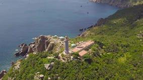 绿色山和蓝色海鸟瞰图岩石海岸的灯塔  飞行在高山的海灯塔的寄生虫 股票视频