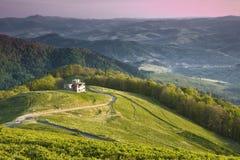绿色山的小屋在黎明在五颜六色的天空下 库存照片