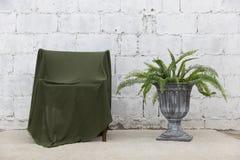 绿色布料盖子正面图与水泥墙壁和花瓶的木椅子 库存照片