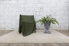 绿色布料盖子正面图与水泥墙壁和花瓶的木椅子 库存图片