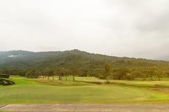 绿色庭院的美好的角落高尔夫俱乐部的与天空和m 免版税库存图片
