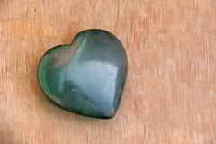 绿色心脏由自然石玉制成 一块心形的石头在棕色或米黄背景说谎 爱护符,禅宗,温泉 免版税库存照片