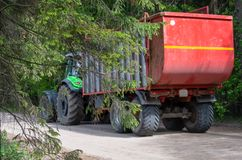 绿色拖拉机运载一辆红色拖车 库存照片