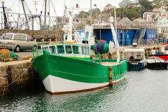 绿色拖网渔船停泊了longside港口墙壁,Brixham,南德文郡 库存照片