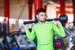 绿色摆在的一个年轻人在与锤子的健身房 免版税库存图片