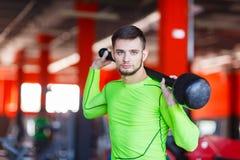 绿色摆在的一个年轻人在与锤子的健身房 免版税库存照片