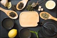 绿色日本和中国茶用传统食物在黑桌上设置了 与拷贝空间的顶视图 图库摄影