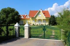 绿色有石柱子的金属加工的篱芭在有车库的现代郊区家庭房子前面 免版税库存图片