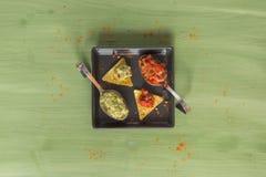 绿色木表面上安排的烤干酪辣味玉米片芯片 免版税库存图片