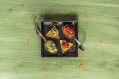 绿色木表面上安排的烤干酪辣味玉米片芯片 免版税库存照片