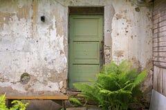 绿色木门,肮脏的难看的东西灰泥墙壁背景 库存图片