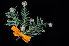 绿色杜松分支与一把黄色弓的由织品和白色塑料雪花制成以花束的形式 库存图片