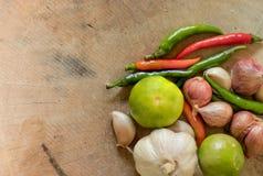 绿色柠檬、新鲜的辣椒、大蒜和青葱在木 免版税库存照片