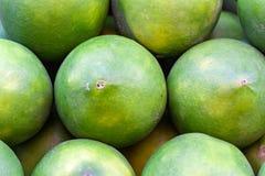 绿色桔子在市场上 库存图片