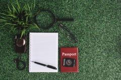 绿色植物、照相机、放大镜、指南针、护照和空白的笔记本在绿草 免版税库存图片