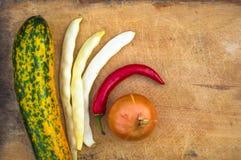 绿色橙色夏南瓜、白豆荚、葱和红色辣椒 免版税库存照片