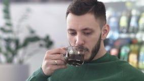 绿色毛线衣的帅哥有咖啡的 影视素材