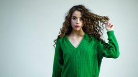 绿色毛线衣的时尚妇女 有卷发的,在她的牙的括号快乐的美女,包裹在手指的头发 影视素材