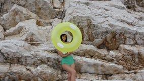 绿色泳装和一个大帽子的亭亭玉立的美丽的浅黑肤色的男人对照相机微笑通过可膨胀的黄色浮游物或 股票录像