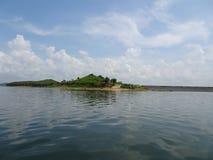 绿色海岛和一条路有水和天空的 库存照片