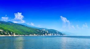绿色海岸线在风平浪静在温暖的夏日 美妙的浪漫风景全景 免版税库存图片