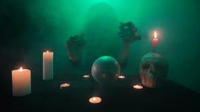 绿色烟的可怕巫婆,召唤在一个水晶球、隐密桌与头骨和蜡烛,快动作 影视素材