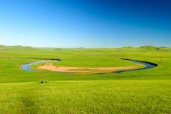 绿色牧场地的蓝色河 库存图片