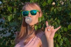 绿色玻璃的女孩与长的头发喘气chewi泡影  免版税图库摄影