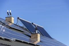 绿色电和水加热的一代的太阳设施在住宅房子关闭的屋顶 免版税库存照片