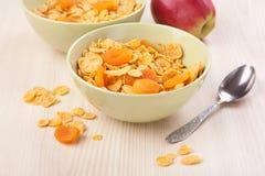 绿色碗嘎吱咬嚼的玉米片早餐用苹果 库存照片