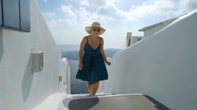绿色礼服和太阳帽子的愉快的妇女享受她的在圣托里尼,希腊的假日 在破火山口和爱琴海的看法从 股票视频