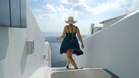 绿色礼服和太阳帽子的愉快的妇女享受她的在圣托里尼,希腊的假日 在破火山口和爱琴海的看法从 影视素材