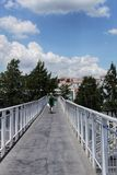 绿色礼服横渡的白色桥梁的妇女 免版税库存图片