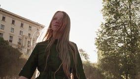 绿色礼服爱抚头发的年轻俏丽的姜女孩在城市广场 股票视频