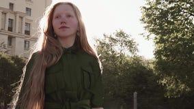 绿色礼服的年轻人相当狡猾的女孩走在城市广场的 股票视频