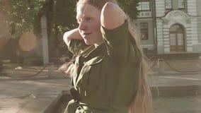 绿色礼服的年轻俏丽的姜女孩走在喷泉附近的 股票录像