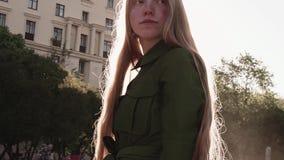 绿色礼服的年轻俏丽的姜女孩走在城市广场的 影视素材
