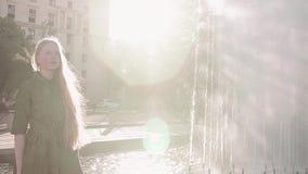 绿色礼服的年轻俏丽的红头发人女孩走在喷泉附近的 影视素材