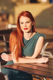 绿色礼服的美丽的年轻红发妇女 免版税库存照片