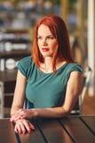 绿色礼服的美丽的年轻红发妇女 库存图片